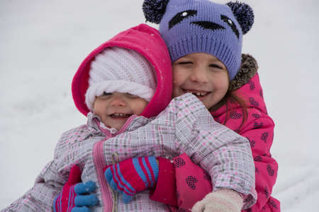 Happy sisters ouside in winter having fun playing 写真素材