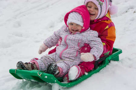 Little sisters child girls playing on sledge outside in winter on snow having fun 写真素材