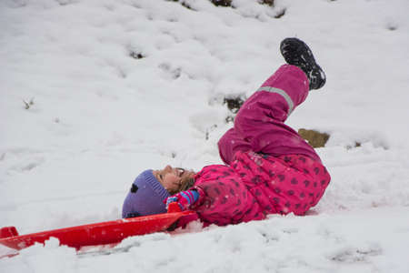 Child girl fall down on hill sliding on snow, laying and smiling having fun from accident 写真素材