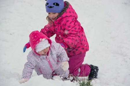 Little girls playing in snow helping little sister in winter outdoor