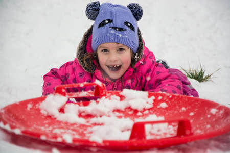 Excited happy child sliding on snow playing outside in winter smiling and having fun