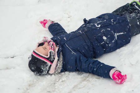 Child girl lays in snow
