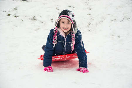 Happy smiling little child on snow in winter playing on hill