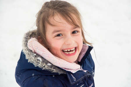 Happy child closeup portrait of girl enjoing winter and snow