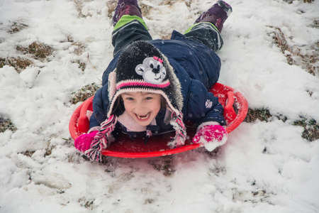 Excited child sliding from hill on snow in winter riding fast 写真素材