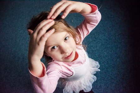 Little cute child girl in ballet dress dancing and looking up smiling; stanging on stage