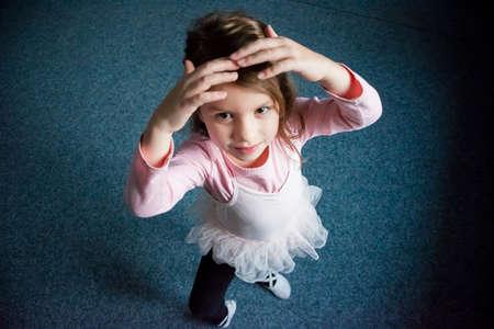 Little kid girl dancing ballet in dress like ballerina