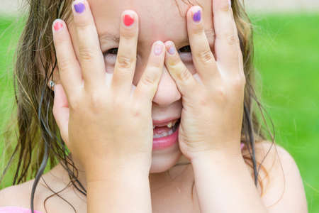 Child girl peeking through her fingers, covering her eyes and face with hands