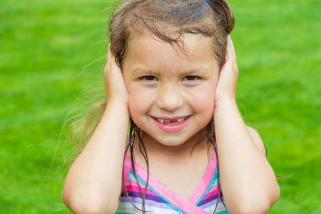 Cute child girl dont hear covering her ears with both hands not listening, but smiling