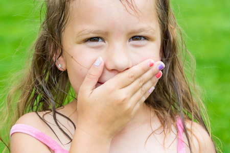 Cute child girl covering her mouth dont speak stopped talking in surprise smiling over funny feelings