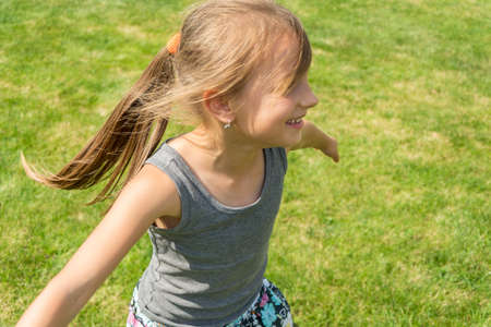 Happy child girl running in garden playing catch-up and twisting