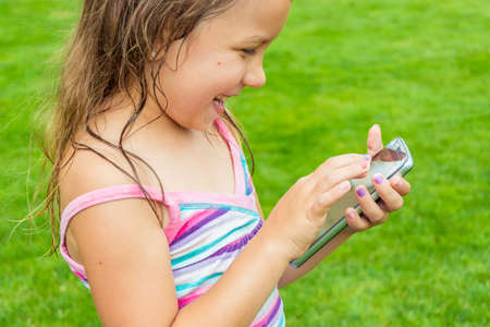 Little child girl enjoing using smart phone, touching screen and smiling outdoor in garden