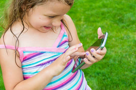 Litte preschooler child girl experimenting with smartphone using it to play with touchscreen device outdoor