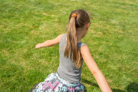 Little child girl with ponytail running in garden shot from back