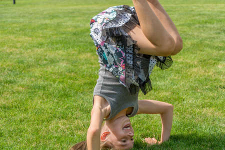 Young child girl standing on her head in garden doing gymnatic and having fun 写真素材