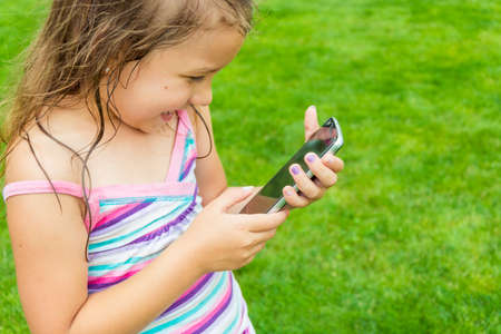 Happy child girl using smart phone in garden, touching screen; shot with copy space 写真素材