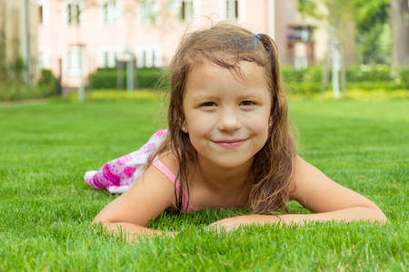 Preschooler child girl laying in grass at city park during summer free time enjoying outdoor 写真素材