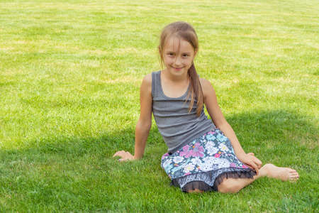 Child girl sitting in grass in shadow during summer