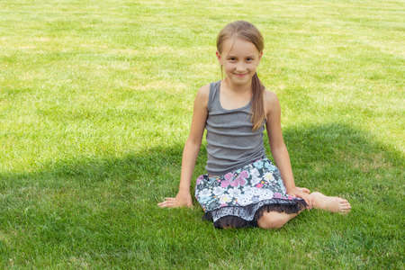 Smiling child girl sitting in grass in shadow during summer 写真素材