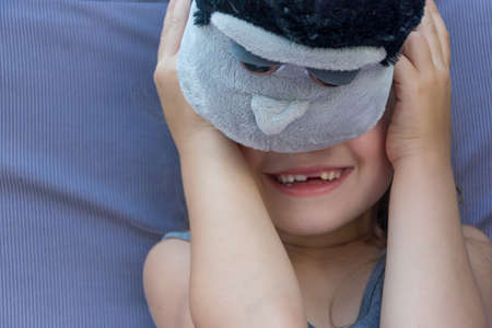Happy shy child girl hiding her face behind the furry toy smiling