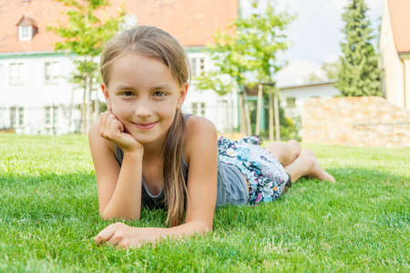 Cute smiling child girl laying in grass at city park during summer enjoying her holiday rest