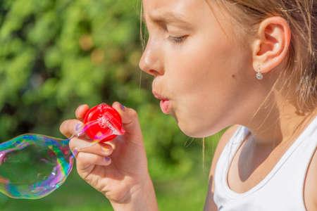 Child girl blowing bubbles in garden closeup