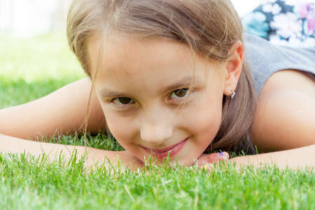 Smiling child girl laying in grass closeup of face