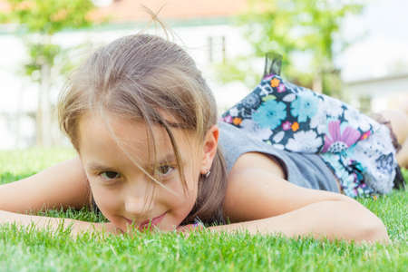 Happy child girl in dress lays in grass at city park enjoing sun and summer holiday