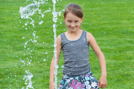Happy smiling child girl with fountain stream of water having fun