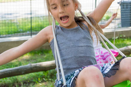 Happy child girl playing on swing outside, screaming in joy