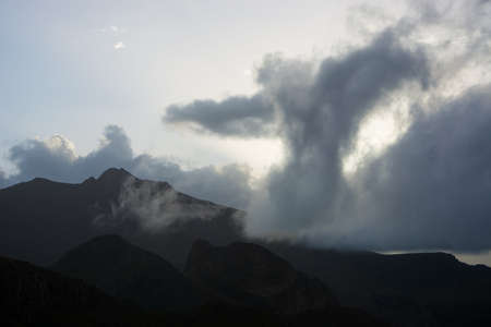 Cloud formation shape of figure or angel above mountain ridge