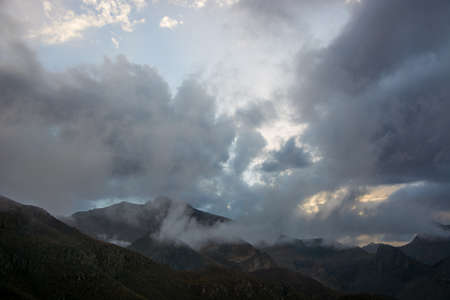 Clouds in the evening light at sky above mountain ridge