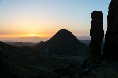 Sunset over Morocco Antiantlas mountains sun behind sharp hill with rock formation silhouette of rocking stone