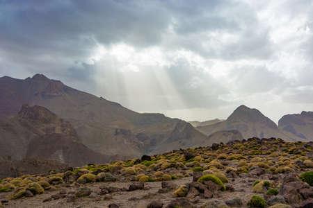 Sun beams shining through clouds above mountain ridge in Morocco Antiatlas mountains 写真素材