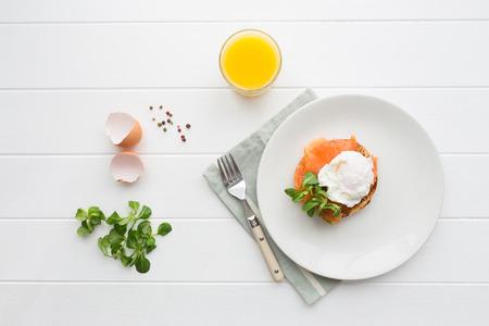Ansicht von oben gesundes Frühstück mit pochierten Eiern royale Benedikt, frisch gepresster Orangensaft und grünem Salat