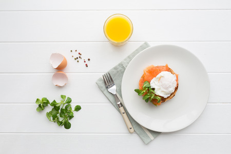 orange juice: Top view of healthy breakfast with poached eggs royale  benedict , fresh orange juice and green salad