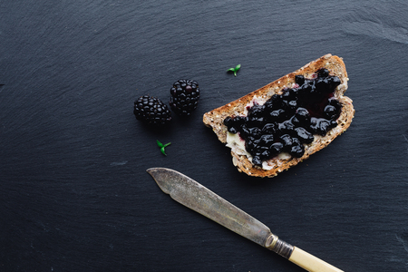 black berry: Healthy breakfast with blue berry jam with toast on black slate background viewed from top