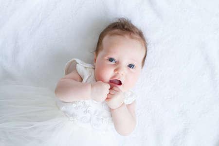 Blue eyed baby meisje in een witte jurk
