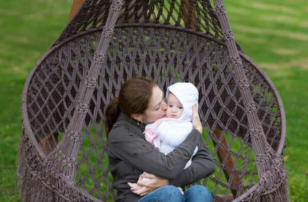Mother and baby in a hanging chair into the park photo