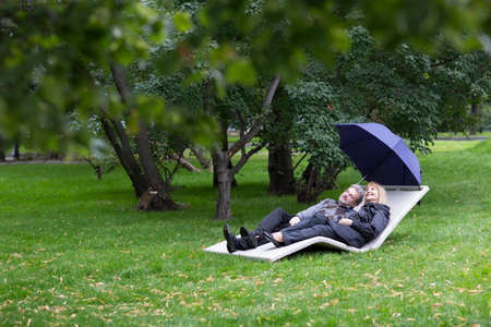 love in rain: Mature couple relaxing on a deck chair under umbrella