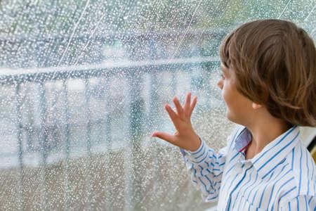 Smiling boy watching the rain outside at a window Banco de Imagens - 29534489