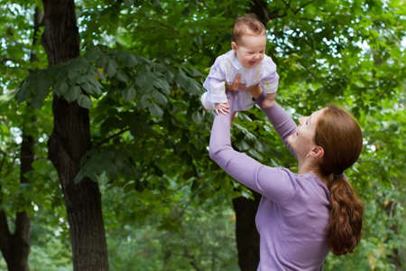 mom holding baby: Young mother playing with a laughing baby girl in a park  Stock Photo