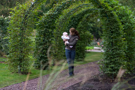 Mother and baby walking through an ivy overgrown archway  photo