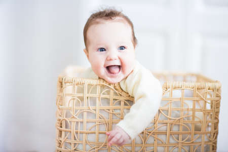 Adorable laughing baby sitting in a laundry basket  photo