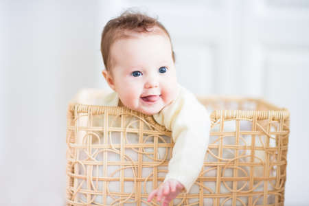 Beautiful little baby smiling out of a wicker basket  photo
