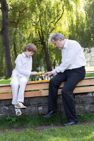 jugando ajedrez: Muchacho lindo que juega al ajedrez con su abuelo en un parque
