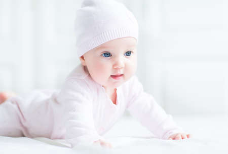 warm cloth: Happy smiling baby girl in a pink knitted hat  Stock Photo