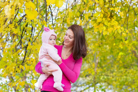 Mother and baby daughter standing under a yellow tree on a sunny autumn day  photo