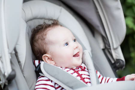 Happy laughing baby sitting in a stroller  photo