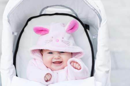 バニー ドレスで白いベビーカーに座っている女の幸せな赤ちゃんを笑ってください。